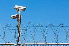 Barbed wire fence with security camera on blue sky Stock Photo