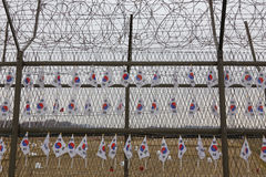 Barbed wire fence separates South from North Korea - South Korean flags attached to fence - Asia- NOVEMBER 2013 Stock Photo