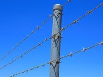 Barbed wire fence. A barbed wire fence at a property in Australia. Low-angle shot against a clear blue sky Royalty Free Stock Photo