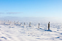 Barbed wire fence with snow covered ground Royalty Free Stock Images