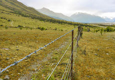 Barbed wire fence stretching towards snow capped mountains Royalty Free Stock Photos