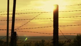 Barbed wire fence at sunset. 4k stock footage