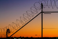 Barbed wire fence at sunset. Barbed wire security fence at sunset Royalty Free Stock Photos