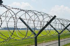 Barbed Wire. Fence with barbed wire on top on blue sky background Stock Photography
