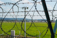 Barbed Wire. Fence with barbed wire on top on blue sky background and CCTV camera Royalty Free Stock Images