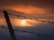 Barbed wire fence with Twilight sky to feel Silent and lonely and want freedom.  Stock Images