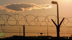 Barbed wire fence with Twilight sky to feel Silent and lonely and want freedom. Barbed wire steel wall against the. Immigration in Europe stock video footage