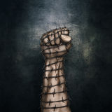 Barbed wire fist. 3D illustration of grungy raised fist wrapped in barbed wire against dark stone background Stock Images