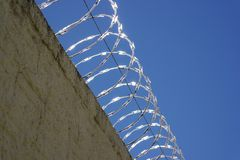 Barbed Wire Protects a Residence from Intruders. Barbed wire installed on a high wall protects a residence from intruders Royalty Free Stock Photography