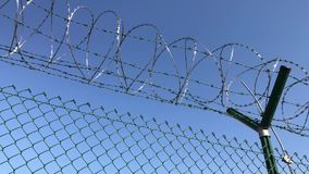 Barbed wire on net fence under blue sky. Taken close up. Protection barrier for access limitation. Chain link guard with barbed wire. Security fence for stock footage