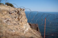 Barbed wire netting on coast. Barbed wire netting limiting the passage to on coast Royalty Free Stock Photography