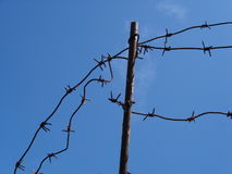Barbed wire. Old rusty barbed wire and an iron bar against the blue sky Stock Photos