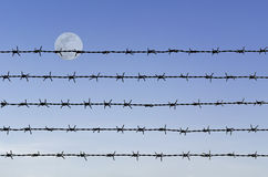 Barbed wire over abstract full moon sky. Row of rustic barbed wire over abstract full moon sky background Stock Photo