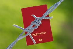 Barbed wire with passport. On green blurred background Royalty Free Stock Photos