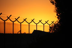 Barbed wire perimeter fence. Under a fierce sunrise Royalty Free Stock Photos