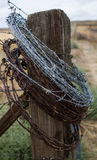 Barbed Wire Post Return. A barbed wire post sits in a field with a bundle of wire attached to it Stock Images