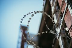 Barbed wire in the prison or on military base, close up perspective. Close up perspective of barbed wire in the prison or on a military base barbwire jail escape royalty free stock photos