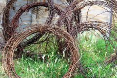 Barbed wire. Rusty reddish brown barbed wire rolled up leaning against an old fence Royalty Free Stock Photography