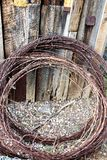 Barbed wire. Rusty reddish brown barbed wire rolled up leaning against an old fence Stock Photography