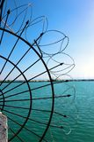 Barbed wire by the sea. Wire netting at the coastline royalty free stock photo