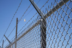 Barbed Wire & Security Lights. Selective focus of fence topped with barbed wire, and security lights in background against blue sky. Horizontal format Stock Image
