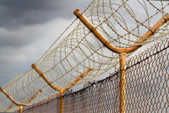 Barbed wire security perimeter fence. Barbed and razor wire security perimeter fence Stock Image