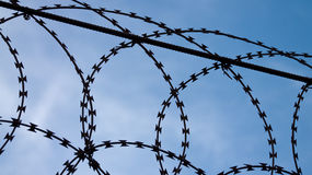 Barbed wire silhouette. A close up view of a barbed wire, silhouetted against the blue sky. Photo taken on November 20th, 2014 Stock Photography