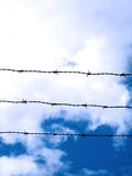 Barbed Wire Sky. 3 strands of barbed wire silhouetted against a dramatic cloudy sky Stock Images