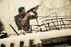 A barbed wire and a soldier in uniform with a gun aim at the shot. Blurred figure in the background. Blue Beret stock photography