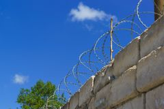 Barbed wire spiral Bruno on top rough high stone walls. Barbed wire spiral Bruno on top rough high stone wall on the sky background Stock Image
