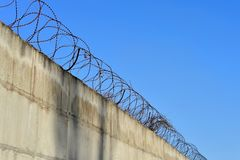 Barbed wire stretched along the brick painted walls Stock Image