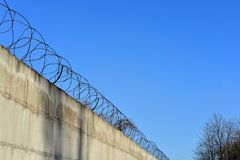 Barbed wire stretched along the brick painted walls Royalty Free Stock Photography