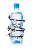 Barbed wire surrounding bottle of water Stock Photos