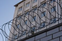 The barbed wire is taut on the fence with coils on the background of the building royalty free stock image