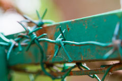 Barbed wire on the top part of a fence Royalty Free Stock Images