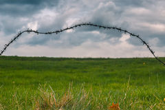 Barbed wire trembling in the wind on the dark stormy clouds background Stock Image