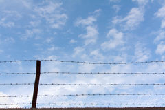 The barbed wire wall. Sky behind the barbed wire wall Stock Photo
