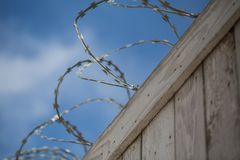 Barbed wire on a fence - close up. Barbed wire on a  wooden fence, prison, freedom outside this fence Stock Photo