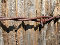 Barbed wire on wooden post. Strand of rusty barbed wire wound around wooden post Royalty Free Stock Photo