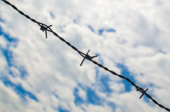 Barbed wires against cloudy sky Stock Photo