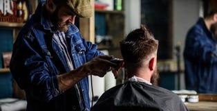 Barbeiro com cabelo do aparamento da tosquiadeira do cliente, vista traseira Cliente do moderno que obtém o corte de cabelo Conce fotografia de stock