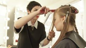 Barbeiro da mulher que usa a lâmina para cortar o cabelo longo no estúdio da beleza Feche acima do penteado fêmea no salão de bel video estoque