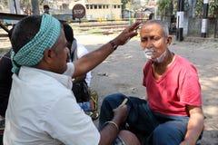 Barbeiro da rua que barbeia um homem que usa uma lâmina de lâmina aberta em uma rua em Kolkata Fotos de Stock