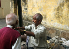 Barbeiro da rua que barbeia um homem que usa uma lâmina de lâmina aberta em uma rua em Kolkata Imagens de Stock
