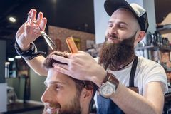 Barbeiro dedicado que usa tesouras e pente ao dar um corte de cabelo fresco imagem de stock