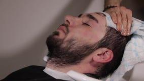 Barbeiro do cabeleireiro que lava o cabelo moreno dos homens sobre o dissipador na barbearia vídeos de arquivo