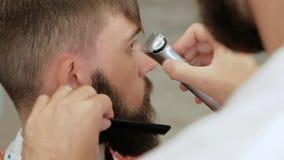 Barbeiro do close-up que apara templos de um homem corajoso farpado à moda com lâmina elétrica vídeos de arquivo