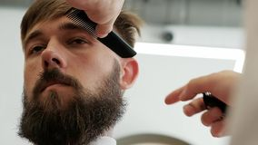 Barbeiro do close-up que apara templos de um homem corajoso farpado à moda com lâmina elétrica video estoque