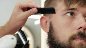 Barbeiro do close-up que apara templos de um homem farpado à moda com lâmina elétrica filme