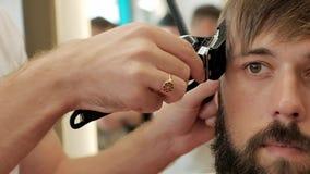 Barbeiro do close-up que apara templos de um homem farpado à moda com lâmina elétrica vídeos de arquivo